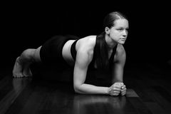 Woman Planking. During working out, isolated on a black background stock image