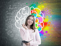 Woman with a planner, colorful brain sketch. Portrait of a dreamy girl in a pink sweater holding a planner and a pen and standing near a blackboard with a stock photography