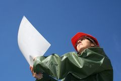 Woman with plans. Woman holding plans with red safety helmet and green plastic raincoat stock image