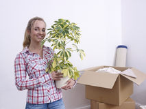 Woman with plant and boxes. Young woman holding a houseplant with opened moving boxes in a white room Royalty Free Stock Photo