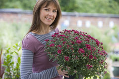 Woman with plant in garden center, smiling, portrait Royalty Free Stock Photography