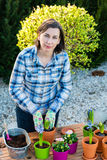 Woman planting flower bulbs - looking at camera Stock Image