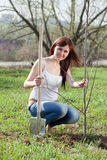 Woman planting tree outdoor. Middle age woman planting tree outdoor Royalty Free Stock Image