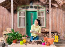 Woman with plants and flowerpots standing at table on porch Royalty Free Stock Photography