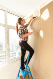 Woman plastering wall on high ladder Royalty Free Stock Photography