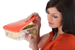 Woman with a plastic box. Brunette looking inside airtight plastic box Stock Image