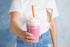 Woman with plastic cup of tasty milk shake on color background royalty free stock photo