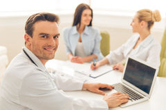 Woman at the plastic surgeon. Handsome doctor is using a laptop, looking at camera and smiling. In the background female doctor is giving a consultation to woman Royalty Free Stock Image