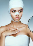 Woman after plastic surgery, looking in mirror. Photo of woman wrapped in medical bandages. Plastic Surgery concept Stock Image
