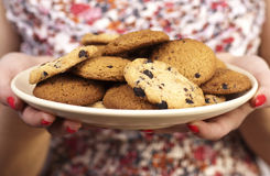 Woman with plate of cookies. Close up royalty free stock image