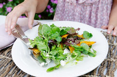 Woman with plate of fresh healthy salad. Close up of woman eating healthy green raw salad Stock Photos