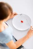 Woman with plate and one tomato Stock Image