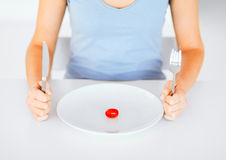 Woman with plate and one tomato Stock Images