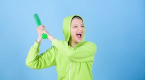 Woman play baseball game or going to beat someone. Girl hooded jacket hold baseball bat blue background. Woman in royalty free stock photo
