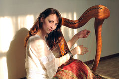 Woman play celtic harp. Woman plays celtic harp in folk style Royalty Free Stock Image