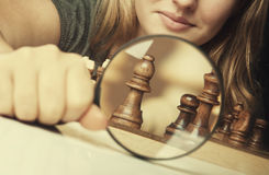 Woman play chess. And hold loupe background Stock Photography