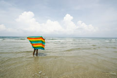 Woman play colorful cloth on beach Stock Images