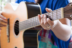 Woman play guitar, closed-up hand on fretboard Stock Photos