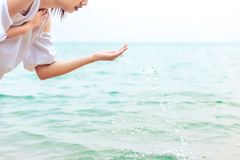 The women play ladle sea water. The woman play ladle sea water ane wear white dress Royalty Free Stock Photos