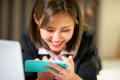 Woman play mobile game happily. On her business trip royalty free stock photo