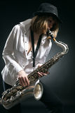 Woman play on saxophone Stock Images