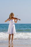 Woman play violin on beach. Young beautiful female violinist play violin on beach Stock Photo