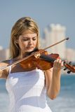 Woman play violin on beach. Young beautiful female violinist play violin on beach Royalty Free Stock Photography