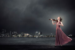 Woman play violin Stock Images