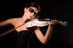 Woman play on white violin. Portrait of sexy woman with black party mask on face play on white violin, isolated on black Royalty Free Stock Image