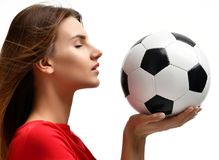Woman player in red uniform hold soccer ball celebrating looking at the corner closeup composition on white background Stock Photo
