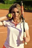 Woman player with tennis racket and ball on court. Girl with net shadow on face on sunny day. Fashion, beauty, look. Activity, energy, health. Sport, game Stock Photos