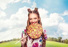 Woman with playful look bites huge candy Stock Image