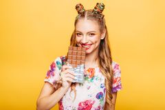 Woman with playful look bites huge chocolate Stock Image