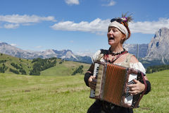 Woman playing accordion, yodeling in Alps Stock Photos