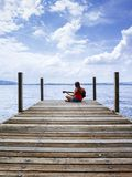 Woman playing acoustic guitar by the lake Stock Photos