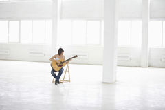 Woman Playing An Acoustic Guitar In Spacious Warehouse Royalty Free Stock Images