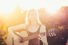 Woman playing acoustic guitar in summer park outdoor.  stock photos