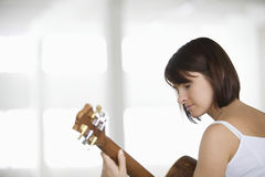 Woman Playing An Acoustic Guitar In Warehouse Royalty Free Stock Photo