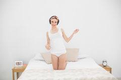 Woman playing air guitar while listening to music Stock Images