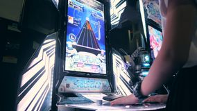 Woman Playing Arcade Machine Game and Pushing Bright Controller Buttons. 4K. Game Zone in MBK Shopping Center. Bangkok. Thailand - 15 NOV 2017 stock footage