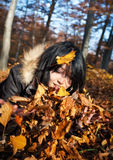 Woman playing with autumn leaves Stock Images