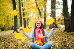 woman playing with autumn leaves in forest stock photo