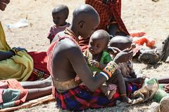 Masai Woman playing with baby , People of Maasai Tribe sitting on ground, Tanzania, Africa royalty free stock images