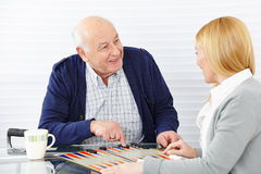 Woman playing backgammon. With senior citizen in a retirement home Stock Images