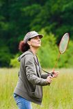 Woman playing badminton. Woman with cap playing badminton in a meadow Stock Photography