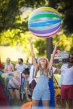 Woman playing with beach ball at campsite. On a sunny day Royalty Free Stock Images