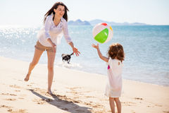 Woman playing with a beach ball. Happy young mother and her daughter playing with a beach ball on a sunny day Royalty Free Stock Image