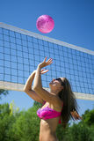 Woman playing beach ball. The young woman in pink bikini is playing beach ball with pink ball Royalty Free Stock Photos