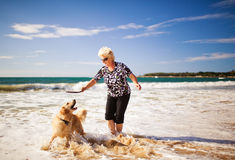 Woman playing on the beach with golden retriever Royalty Free Stock Images