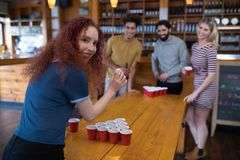 Woman playing beer pong game with friends in bar. Portrait of smiling woman playing beer pong game with friends in bar Stock Photo